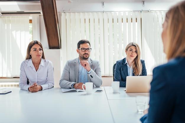Hr managers interviewen vrouwelijke sollicitant.