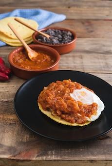 Huevos rancheros gerecht, mexicaans ontbijt op een houten voet. mexicaanse keuken. kopieer ruimte.