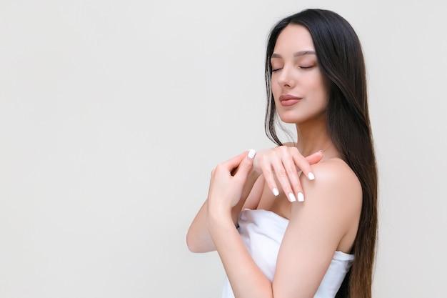 Huid- en lichaamsverzorging. mooie jonge vrouw in een handdoek raakt haar huid aan met haar handen.