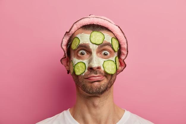 Huid gezondheid concept. verbijsterde emotionele man met wijd geopende ogen, heeft cosmetische behandelingen thuis, reinigt teint met voedzaam masker en komkommer