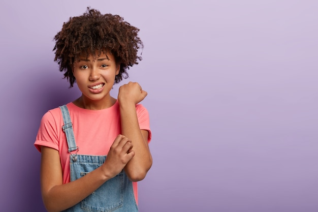 Huid probleem concept. ontevreden afro-vrouw krabt aan jeukende arm