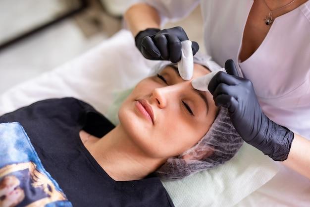 Huid zorg concept. een vrouw in een schoonheidssalon tijdens een behandeling van de gezichtshuidverzorging.