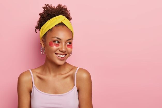 Huid zorg concept. jonge afro-amerikaanse vrouw met collageenkussentjes onder de ogen, wil een schone, frisse huid hebben, draagt een gele hoofdband en een casual vest