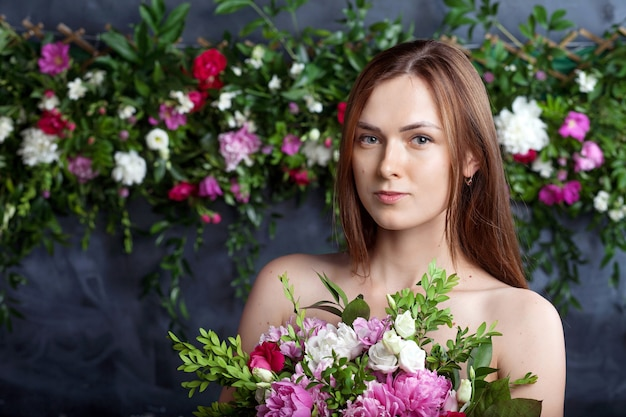 Huid zorg concept. meisje op kalm gezicht staat naakt en houdt bloemen voor de borst. de mooie vrouw met natuurlijke make-up neemt genoegen terwijl het boeket vasthoudt