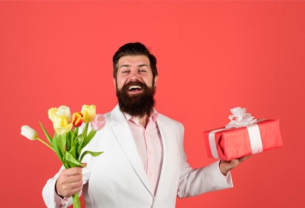 Huidige doos boeket bloemen lachende man houdt valentijnscadeau en bloemen valentijnsdag gelukkig