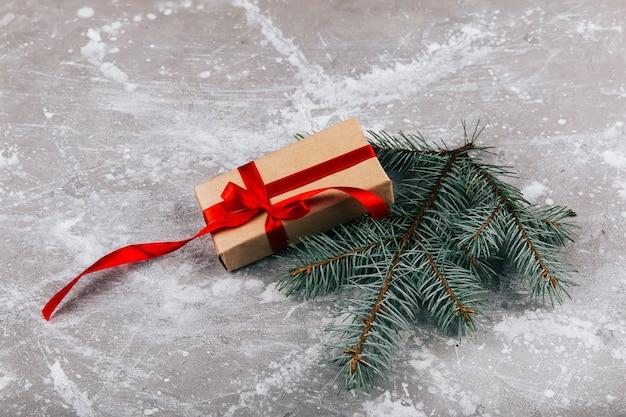 Huidige doos gemaakt van grijsbruin papier en getwijnd met rood lint ligt met een sparentak op een grijze vloer
