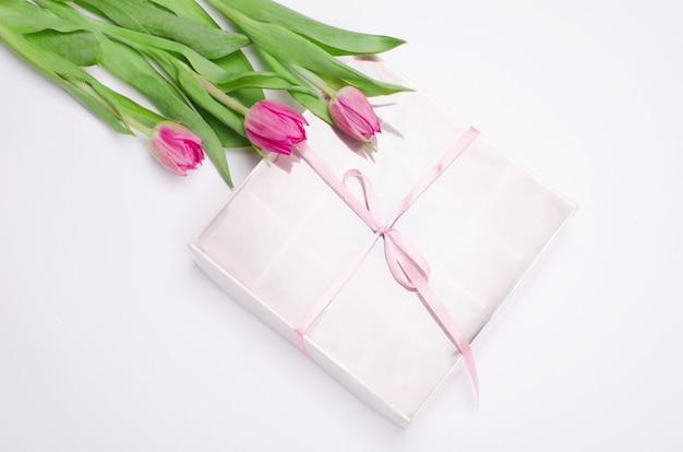 Huidige doos met de harten van chocoladesnoepjes en tulpen op witte lijst. woestijn voor valentijnsdag