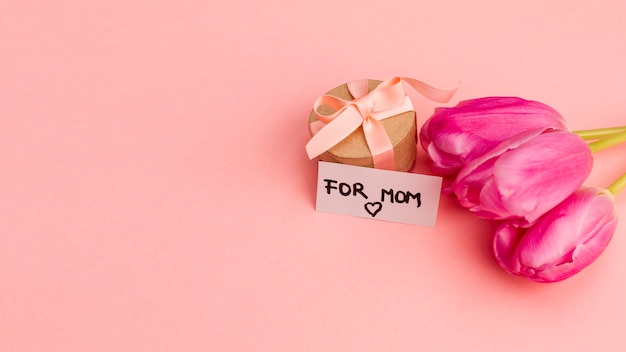 Huidige doos met lint dichtbij nota en bloemen