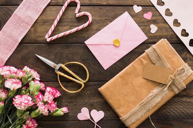 Huidige doos tussen bloemen, envelop en snoepriet