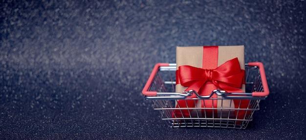 Huidige doos versierd met rood lint en ambachtelijk papier in winkelmandje op donkere rustige achtergrond. verkoopbanner, ruimte voor tekst