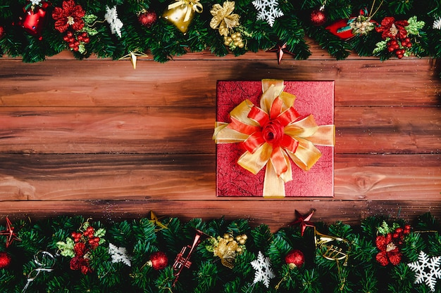 Huidige geschenkdoos met gouden kleur lint op hout achtergrond met kerstboom en traditionele ornamenten xmas rekwisieten met kopie ruimte. concept van gelukkig en vreugdevol in festival.