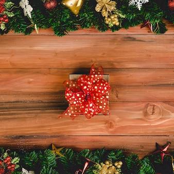 Huidige geschenkdoos met rode kleur lint op hout achtergrond met kerstboom en traditionele ornamenten xmas rekwisieten met kopie ruimte. concept van gelukkig en vreugdevol in festival.