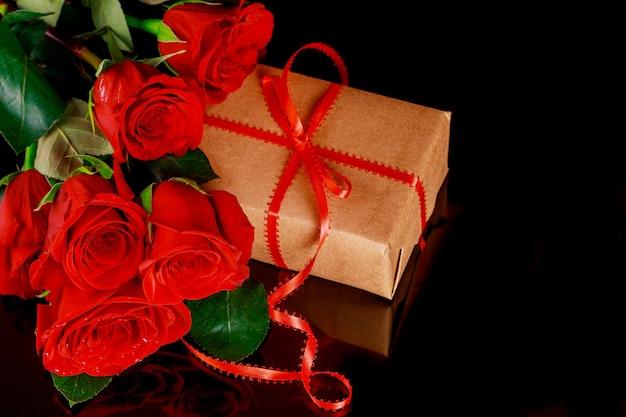 Huidige geschenkdoos met rood lint en boeket van mooie rode rozen. moederdag of valentijnsdag concept.