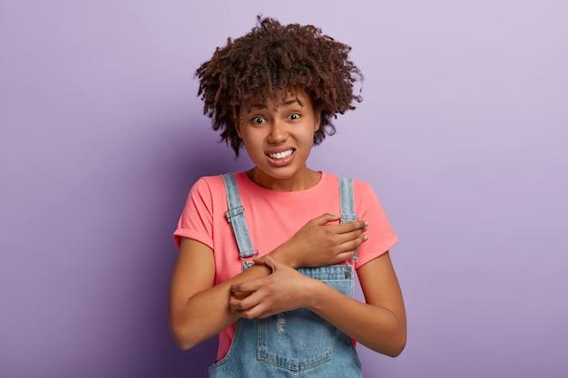 Huidprobleem en dermatologie concept. ontevreden krullende afro-amerikaanse vrouw krassen jeuk op de arm