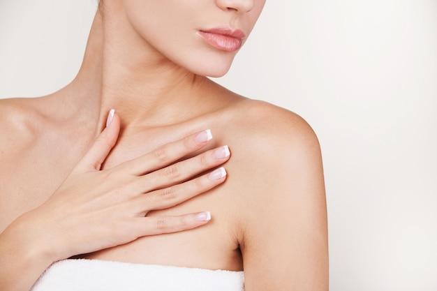 Huidsverzorging. bijgesneden afbeelding van mooie jonge vrouw gewikkeld in een handdoek die tegen een grijze achtergrond staat
