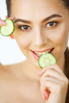 Huidsverzorging. het gelukkige sexy vrouw stellen met plakjes komkommer in haar handen. schoonheidsbehandeling. cosmetologie. schoonheidssalon. thuis spa