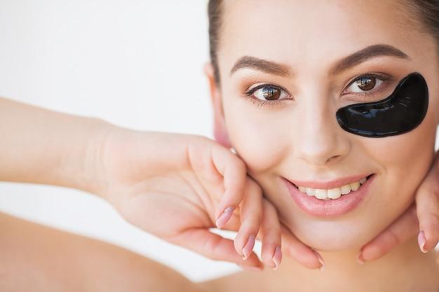 Huidsverzorging. mooi meisje met cosmetische zwarte vlekken onder de ogen, perfecte huid en natuurlijke make-up