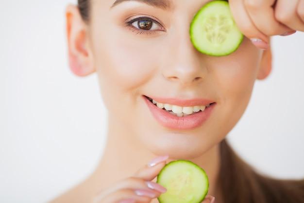 Huidsverzorging. mooie jonge vrouw met komkommers op ogen