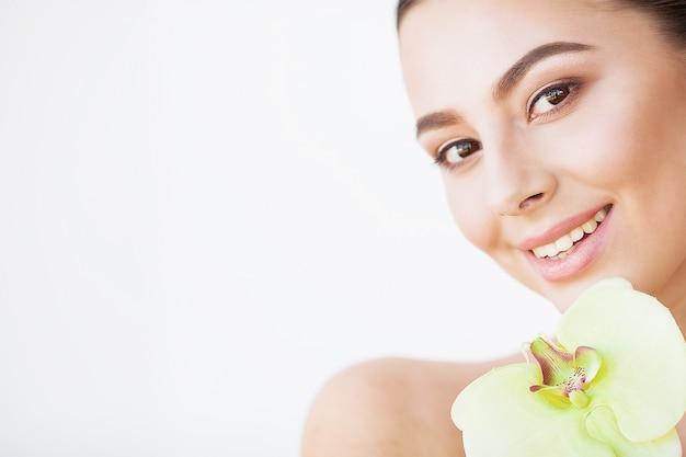 Huidsverzorging. mooie modelvrouw met perfecte huid en orchideebloem dichtbij haar gezicht