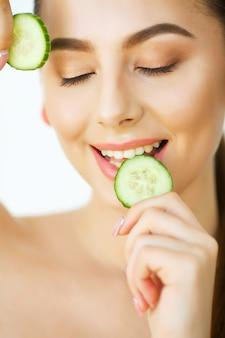 Huidsverzorging. portret mooie gelukkige vrouw met komkommers aan ogen thuis. schoonheidsbehandeling. cosmetologie. schoonheidssalon