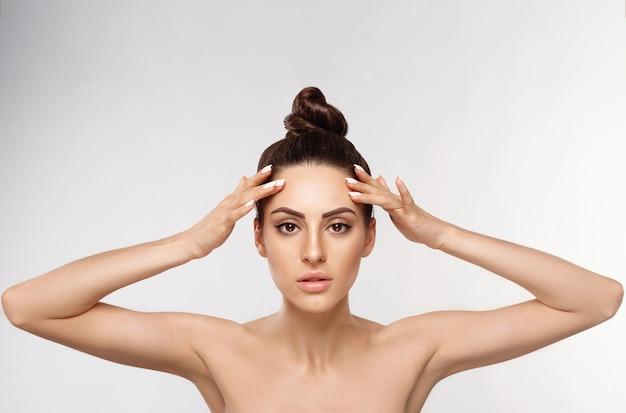 Huidsverzorging. schoonheid concept. zachte huid en blote schouders, model met lichte naakte make-up, portret van vrouw raakt eigen gezicht.