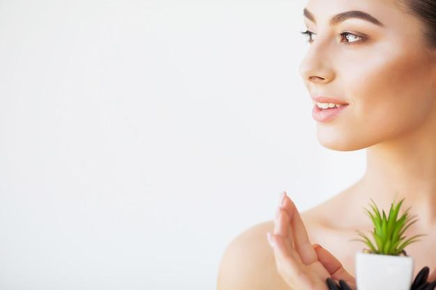 Huidsverzorging. schoonheid vrouw gezicht met gezonde huid en groene plant
