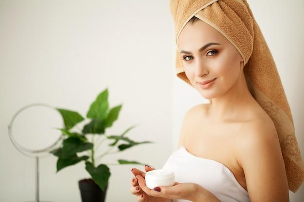 Huidsverzorging. studio die van mooie jonge vrouw is ontsproten die vochtinbrengende crèmeroom op haar gezicht toepast