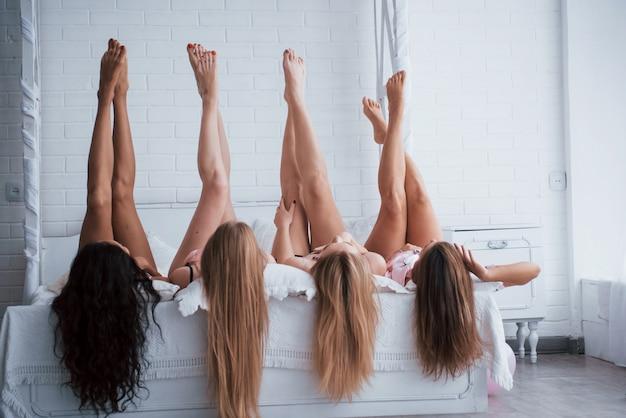 Huidsverzorging. vier jonge vrouwen met een goede lichaamsvorm liggend op het bed met hun benen omhoog