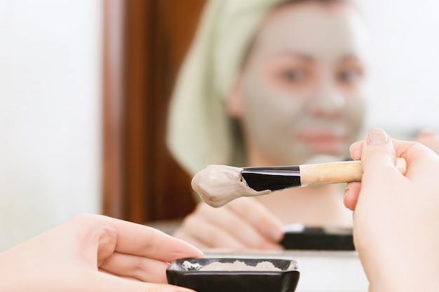 Huidsverzorging. vrouwelijke handen maken klei gezichtsmasker.