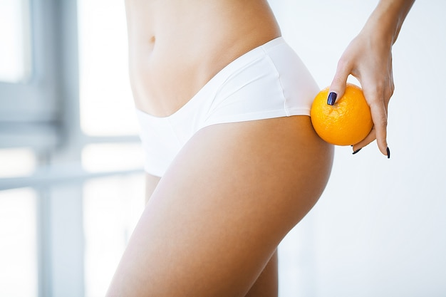 Huidverzorging controle. vrouw die een sinaasappel houdt tegen haar dijen