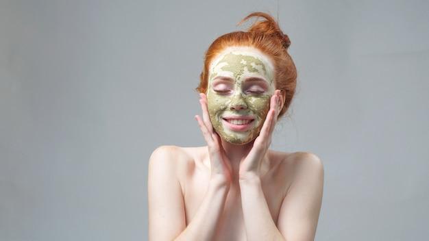 Huidverzorging. een jonge vrouw met een groen-wit moddermasker op haar gezicht.