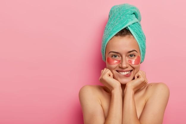 Huidverzorging en cosmetologie concept. gelukkig mooie vrouw past patches onder de ogen toe na het douchen, bijt op de lippen, houdt de handen onder de kin, staat blote schouders tegen roze achtergrond