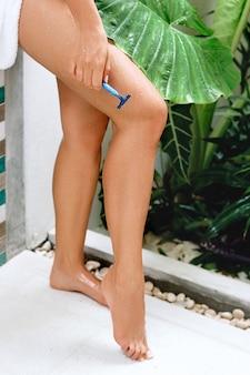 Huidverzorging en gezondheid. ontharing. fit vrouw haar benen scheren met scheermes.