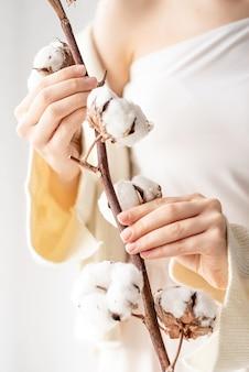 Huidverzorging en jeugdconcept. mooie vrouw handen met tak van katoen bloemen