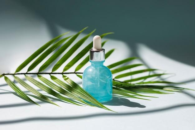 Huidverzorging gezichtsserumfles met palmtak