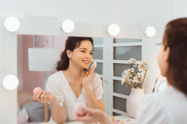 Huidverzorging. jonge vrouw make-up verwijderen met behulp van wattenschijfje staande in de badkamer. panorama, lege ruimte
