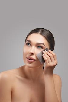 Huidverzorging. jonge vrouw olie verwijderen uit gezicht met behulp van vloeipapier. mooi meisjesmodel met vlotte en gezonde huid.
