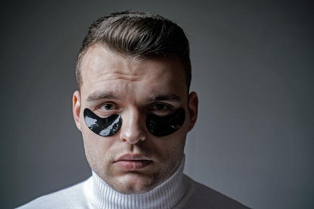 Huidverzorging. minimaliseert wallen en vermindert donkere kringen. ooglapjes voor mannen. man met zwarte ooglapjes close-up gezicht. schoonheidsbehandeling. metroseksueel concept. gerichte behandelingen voor onder de ogen.