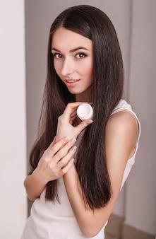 Huidverzorging. mooie gezonde jonge vrouw met lang haar, zorgzaam voor hun huid. gebruik crème voor lichaamsverzorging. schoonheid en gezondheid