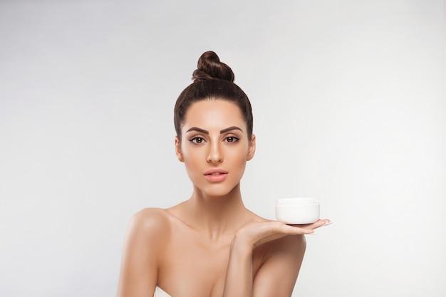 Huidverzorging. mooie jonge vrouw met schone frisse huid holding fles crème