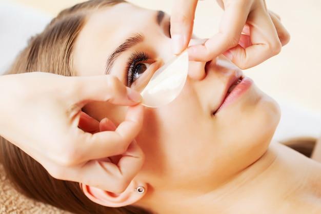 Huidverzorging onder de ogen, vlekken worden aangebracht op de ogen van de jonge vrouw
