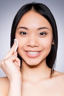 Huidverzorging. portret van een vrolijke jonge en shirtloze aziatische vrouw die lacht naar de camera en haar gezicht aanraakt met een spons terwijl ze tegen een grijze achtergrond staat