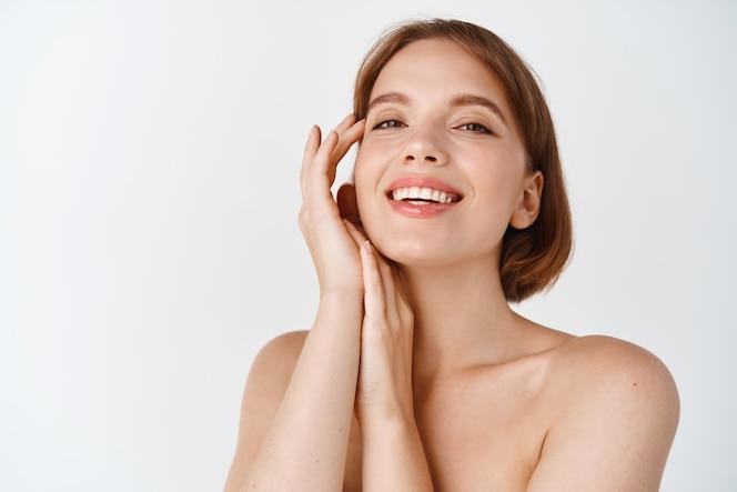 Huidverzorging schoonheid. glimlachende natuurlijke vrouw met blote schouders en een gezonde schone en frisse huid, die er gelukkig uitziet, de wang aanraakt. meisje brengt gezichtscosmetica aan, witte muur