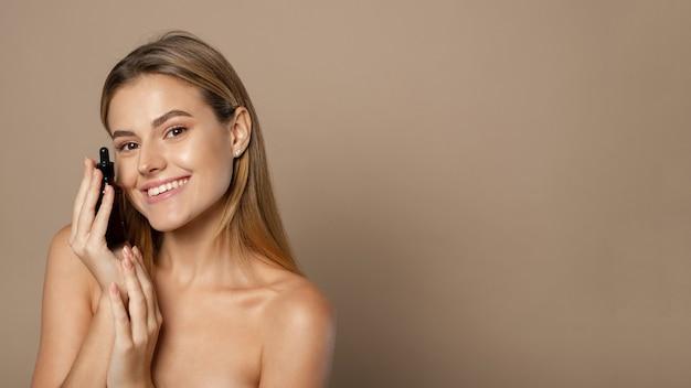 Huidverzorging. schoonheid portret van vrouw met fles met druppelaar