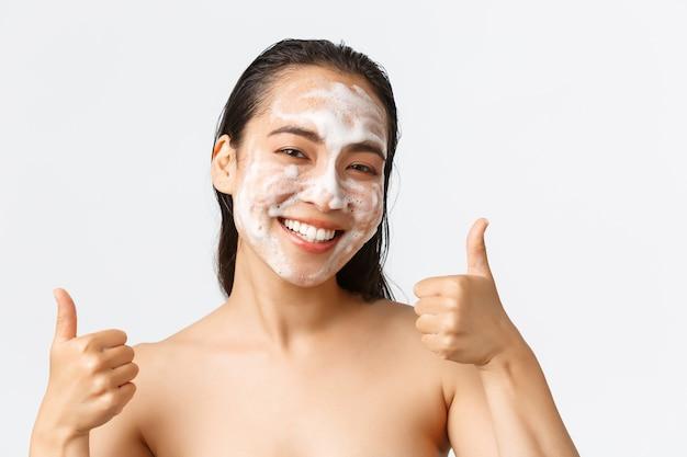 Huidverzorging, schoonheid van vrouwen, hygiëne en persoonlijke verzorging. close-up van tevreden gelukkige, glimlachende aziatische vrouw die naakt staat en duimen toont terwijl ze reinigingsschuim op het gezicht gebruikt.