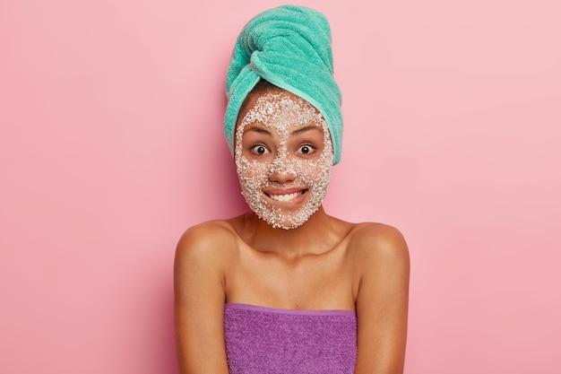 Huidverzorging, schoonheidsconcept. mooie mooie vrouw bijt onderlip, ziet er vrolijk uit, heeft hygiënische behandelingen thuis, reinigt gezicht van vuil en poriën