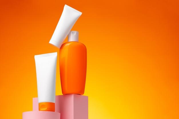 Huidverzorging schoonheidsproducten container tegen roze achtergrond, kopie ruimte