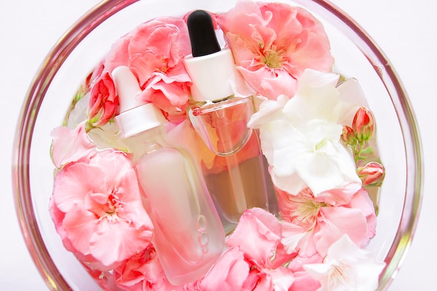 Huidverzorging serum olie met kleine bloemen in glazen plaat. cosmetische spa-gezichtsproduct. huid concept behandeling. druppelaar van etherische olie, aromatherapie-essentie