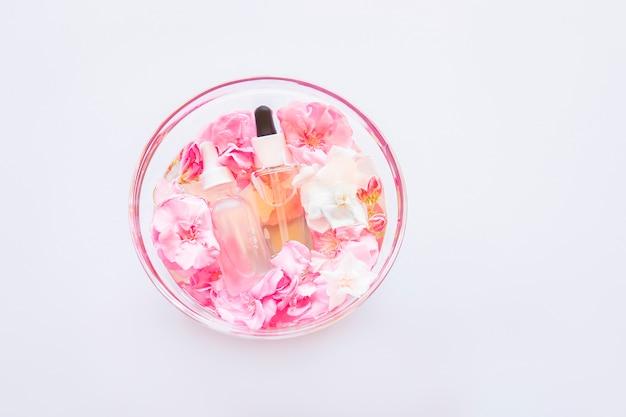 Huidverzorging serum olie met kleine bloemen in glazen plaat. natuurlijke cosmetologie, huidbehandeling.