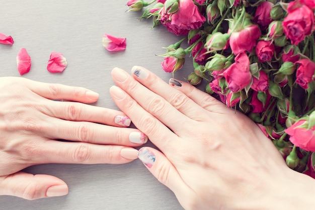 Huidverzorging van een mooie vrouwelijke handen met kunst nagel manicure. en grijze tafel met kleine roze rozen